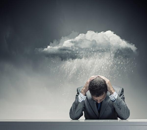 Businessman sitting wet under rain