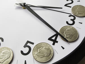 Concept of time is money Eisenhower dollar coins on face of analog clock