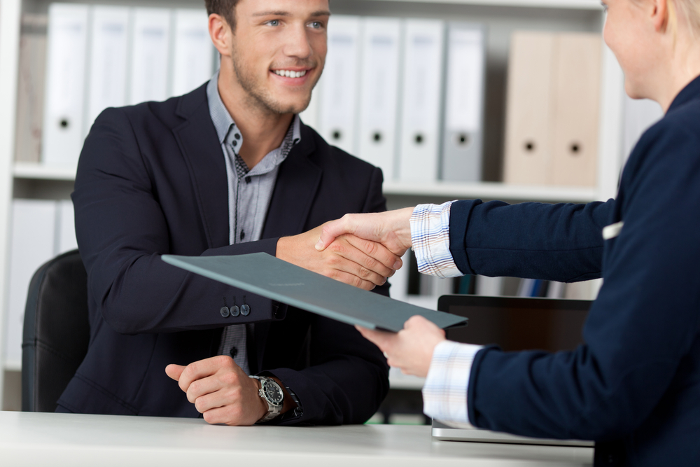 Happy businessman shaking hands with a female interviewer in office