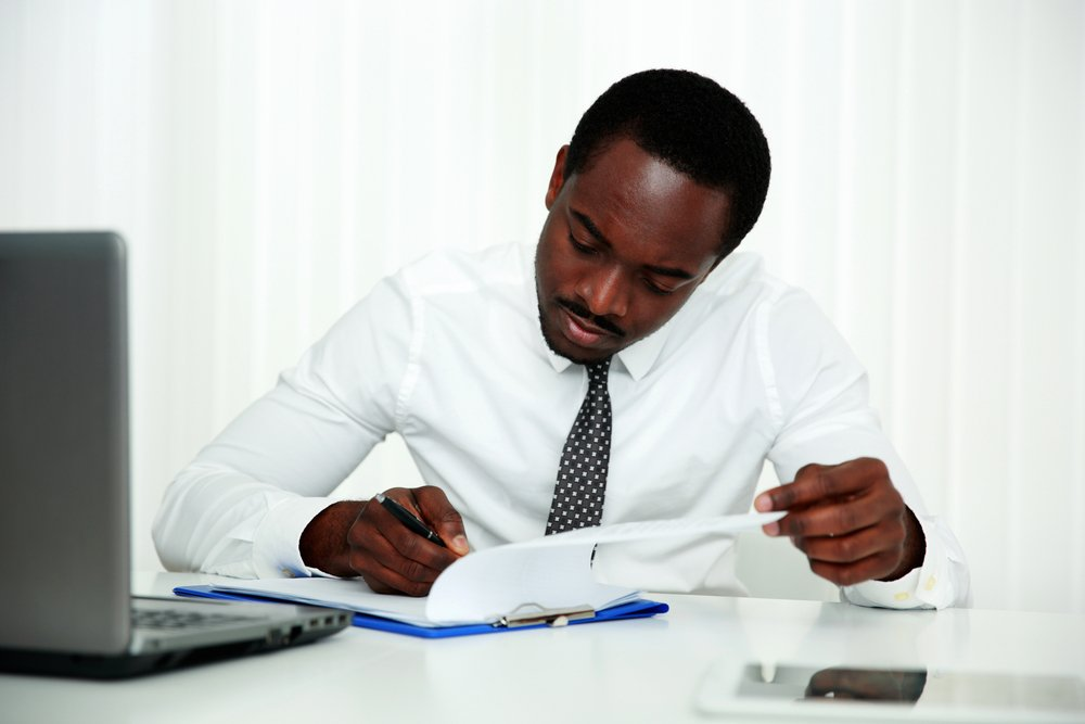 African man signing document in office